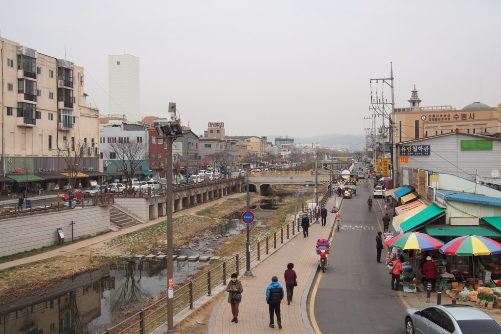 This is the center of Hwaseong Fortress, there are walls and gates surrounding the town's center...